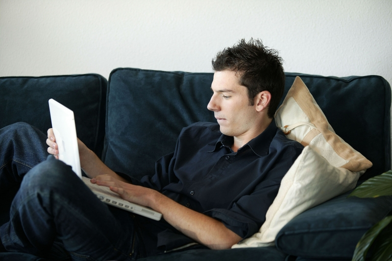3959740-man-sitting-on-his-couch-and-using-his-laptop